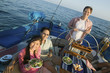Man at helm of sailboat, friends having lunch, portrait