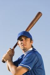 Baseball player swinging baseball bat, low angle view