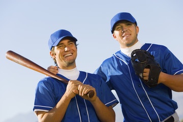 Two baseball team-mates holding baseball bats, low angle view
