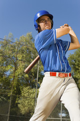Baseball player swinging baseball bat, low angle view