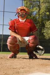 Baseball catcher crouching on baseball field, giving hand signals