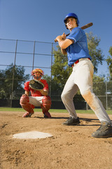 Baseball player swinging baseball bat, catcher crouching in background