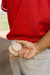 Baseball pitcher holding ball, close-up, mid section