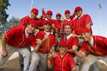 Baseball team-mates holding trophy on field