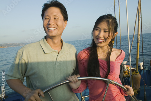 Couple at steering wheel of sailboat, smiling