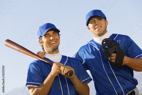 Two baseball team-mates holding baseball bats, low angle view
