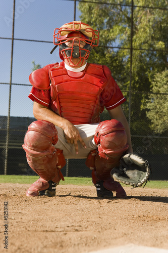 Baseball catcher crouching on baseball field, giving hand signals