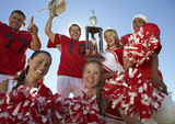 Football players and cheerleaders hoisting trophy, low angle view, portrait, portrait