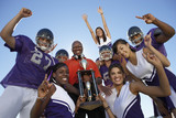 Football coach, players and cheerleaders holding trophy outside, low angle view, portrait, portrait