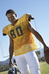 Football player holding helmet and ball standing on field, low angle view, portrait, portrait