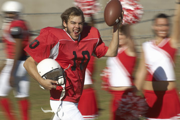 Football player holding ball running by cheerleaders