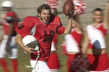 Football player holding ball running by cheerleaders