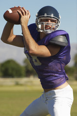 Quarterback throwing ball on field, portrait