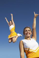Cheerleaders cheering and jumping, mid-air, low angle view