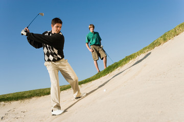 Golfer hitting ball from sand trap