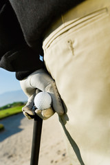 Golfer holding golf ball and club, close-up