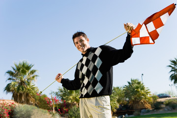 Golfer holding flagstick on shoulders standing on golf course, portrait
