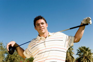 Golfer holding club on shoulders, portrait, low angle view