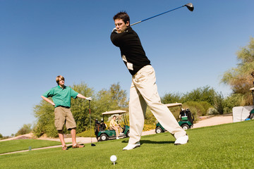 Golfer teeing off next to other player
