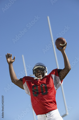Football Player cheering with ball on field, low angle view, low angle view