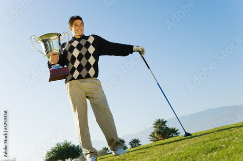 Golfer holding trophy standing on golf course, portrait