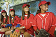 Young female softball players sitting on bench
