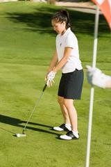 Female golfer putting on green