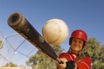 Batter hitting softball, portrait