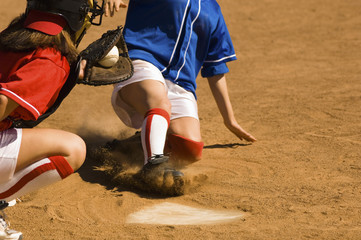 Softball player sliding into home plate, low section