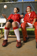 Softball players sitting on bench, low angle view