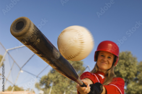 Batter hitting softball, portrait