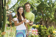 Young couple choosing potted flowers in garden centre, portrait