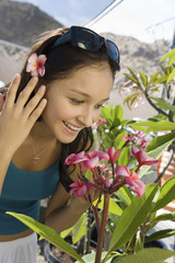 Young woman smelling exotic plat in greenhouse, close-up