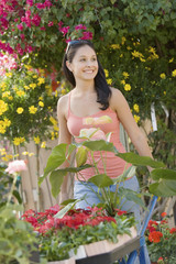 Young woman pushing wheelbarrow with plants