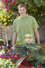Young man pushing wheelbarrow with plants, smiling