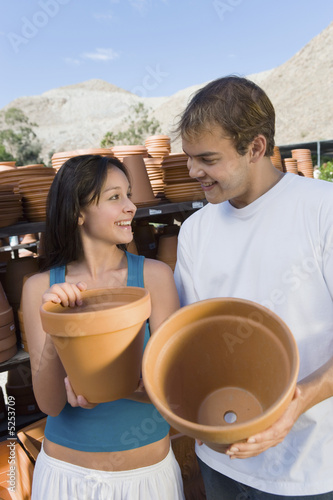 Young couple holding flower pots in outdoors garden centre
