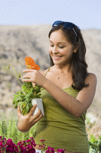 Young woman holding potted plant in garden centre