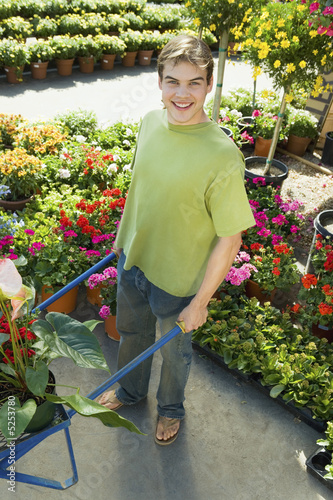 Young man with pushcart in garden centre, portrait, elevated view