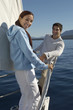 Young couple standing on bow of sailboat, portrait
