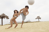 Woman Holding Man Back from Diving for Volleyball on Beach