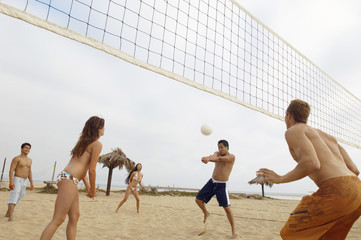 Man Hitting Volleyball during Game on Beach
