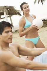 Woman in Bikini Holding Volleyball, man sitting on foreground