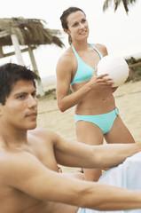 Woman in Bikini Holding Volleyball, man sitting on foreground