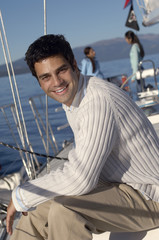 Young man on sailboat, friends in background, portrait