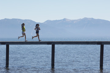 Women Jogging on Pier above Scenic Lake