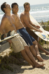 Three surfers leaning on bench holding surfboards on beach
