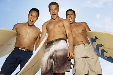 Three surfers standing with surfboards, making faces, outdoors, low angle view