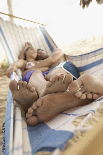 Young couple Sleeping in Hammock on Beach, focus on foreground