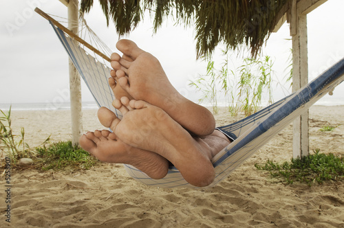 Couple's Feet on Edge of Hammock on Beach