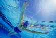 Woman swimming floating underwater, low angle view